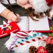 Funny girl in Santa hat writes letter to Santa near christmas decoration — Stock Photo #59326945