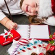 Funny girl in Santa hat writes letter to Santa near christmas decoration — Stock Photo #59327001