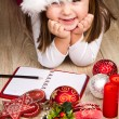 Funny girl in Santa hat writes letter to Santa near christmas decoration — Stock Photo #59327035
