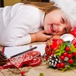 Funny girl in Santa hat writes letter to Santa near christmas decoration — Stock Photo #59327065