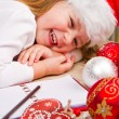 Funny girl in Santa hat writes letter to Santa near christmas decoration — Stock Photo #59327095