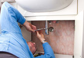 A plumber repairing a broken sink in bathroom  — Stock Photo