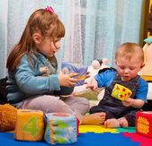 Brother and sister playing with soft colored cube — Stock Photo