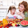Mother gives to the little girl a fruit salad in the kitchen. — Stock Photo #74258379