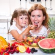 Mother gives to the little girl a fruit salad in the kitchen. — Stock Photo #74258455