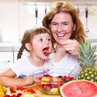 Mother gives to the little girl a fruit salad in the kitchen. — Stock Photo #77441444