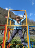 Cute little girl is climbing  in playground equipment — Stock Photo