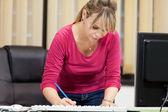 Secrétaire prend debout whie notes à côté de son bureau — Photo