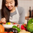 Asian smiling woman is composing a colorful salad  — Stock Photo #63741195