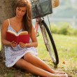 Gorgeous woman is reading a book next to a tree where her bike i — Stock Photo #64073823