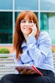 Businesswoman is sitting on a metal bench with charts in her han — Stock Photo