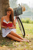 Gorgeous woman is reading a book next to a tree where her bike i — Stock Photo