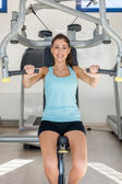 Young smiling brunette is training her upper body — Stock Photo