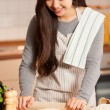 Asian young woman is baking bread in her home kitchen — Stock Photo #64782655