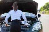 Businesswoman is looking inside the car hood — Stock Photo