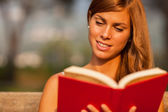 Brunette woman is reading a book on a bench — Foto Stock