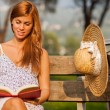 Brunette woman sitting on a bench with a book — Stock Photo #65911797