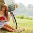 Gorgeous woman is reading a book next to a tree where her bike i — Stock Photo #66346403