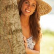 Beautiful smiling girl with hat behind a tree — Stock Photo #66884363