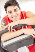Caucasian man is smiling while sitting on a gym bicycle — Stock Photo