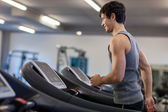 Trained man is running on a treadmill — Stock Photo