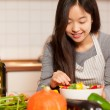 Asian smiling woman is composing a colorful salad  — Stock Photo #68087925