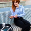 Businesswoman sitting outside on a metal bench while smiling — Stock Photo #68088049