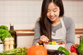Asian smiling woman is composing a colorful salad  — Stock Photo