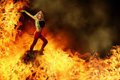 Blonde female devil is dancing in the fire — Stock Photo