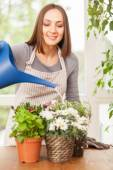 Caucasian smiling woman is pouring water in the plants — Stock Photo