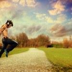 Shirtless street dancer with headphones over landscape backgroun — Stock Photo #72866465