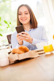 Businesswoman is having breakfast while checking her emails — Stockfoto