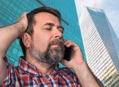 Middle-aged man speaks on a mobile phone — Stock Photo