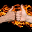Two men bumping fists with thumbs up against the fire flames — Stock Photo #55728737