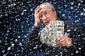 Man with a bundle of dollars in snowfall — Stock Photo