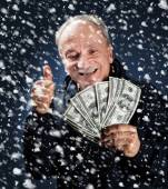 Man med en bunt dollar i snöfall — Stockfoto