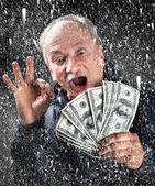 降雪でドルのバンドルを持つ男 — ストック写真