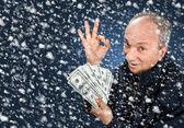 Muž s balíkem dolarů ve sněžení — Stock fotografie
