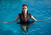 Wet woman in black dress in a swimming pool — Stock Photo