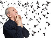 Elderly man looking up on flying birds — Stock Photo