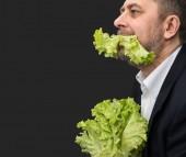 Hombre sosteniendo y comiendo lechuga — Foto de Stock
