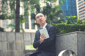 Asian business male using portable computer on park in hong kong — Stock Photo