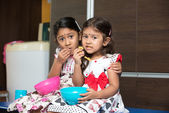 Indian sisters eating — Stock Photo