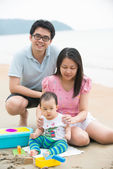 Asian family playing on a beach — Stock Photo