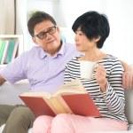 Asian senior couple reading book — Stock Photo #56034827