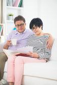 Asian senior couple reading book — Stock Photo