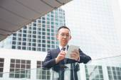Asian businessman with tablet — Stock Photo