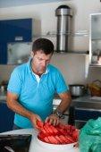 Caucasian man in the kitchen slicing watermelon — Stock Photo