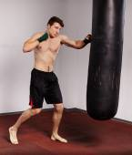 Kickboxer with punch bag — Stock Photo