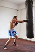 Kickboxer training with punchbag — Stock Photo